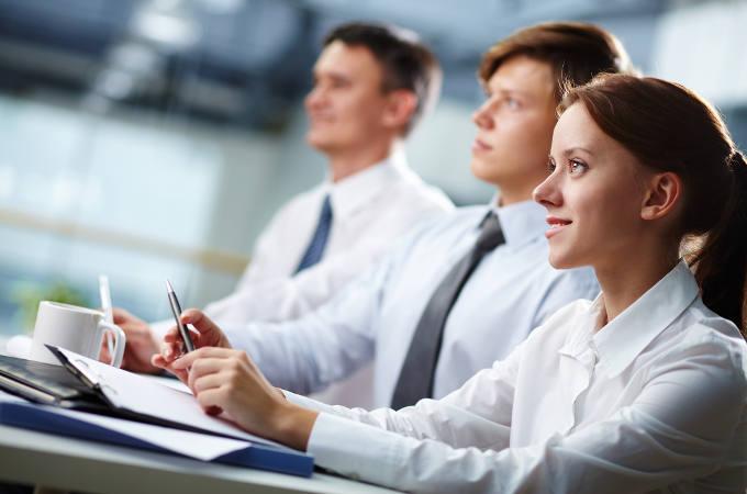 Three business people sitting at a seminar